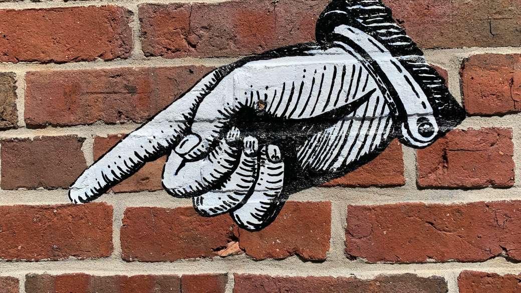 Straßenkunst auf einer Backsteinwand mit einem Finger, der auf etwas zeigt